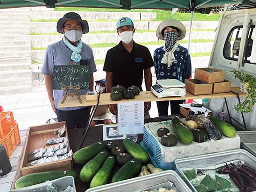 くさつファーマーズマーケットの主催者新喜多さんと、参加農家の河合雲平さんたちの軽トラック