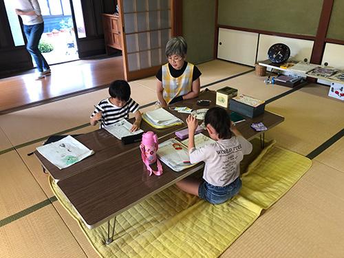 TERAコミュニティー鳥羽上「地域学童保育と集いの場」のようす画像 宿題をする1年生と中嶋さん