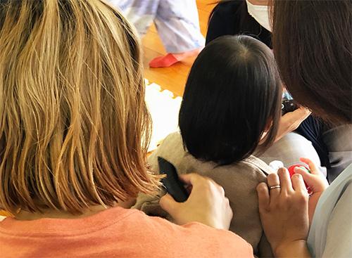 ママミーティング部の活動紹介画像 実際にお子さんの髪をカット中
